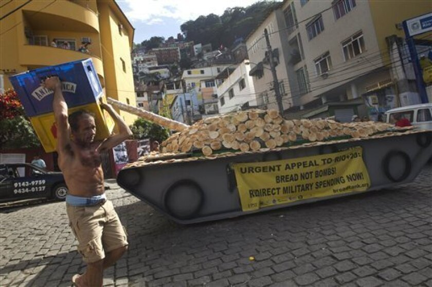 "A worker carries crates past a fake life-sized war tank covered with bread sitting on display in the Santa Marta slum as part of a ""Bread not Bombs"" protest on the sidelines of the Rio+20 UN Conference on Sustainable Development in Rio de Janeiro, Brazil, Tuesday, June 19, 2012. Activists placed th"