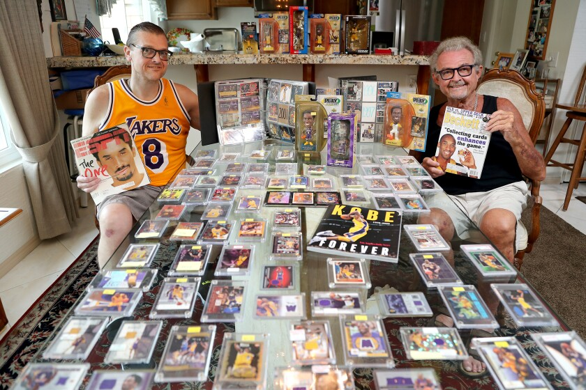 Huntington Beach residents Alex Kolosow and his son, Alex II, sit among Kobe Bryant-related memorabilia.