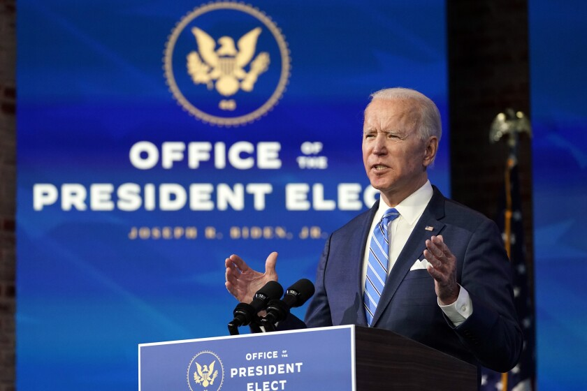 President-elect Joe Biden gestures while speaking at a lectern in front of a screen that says Office of the President Elect