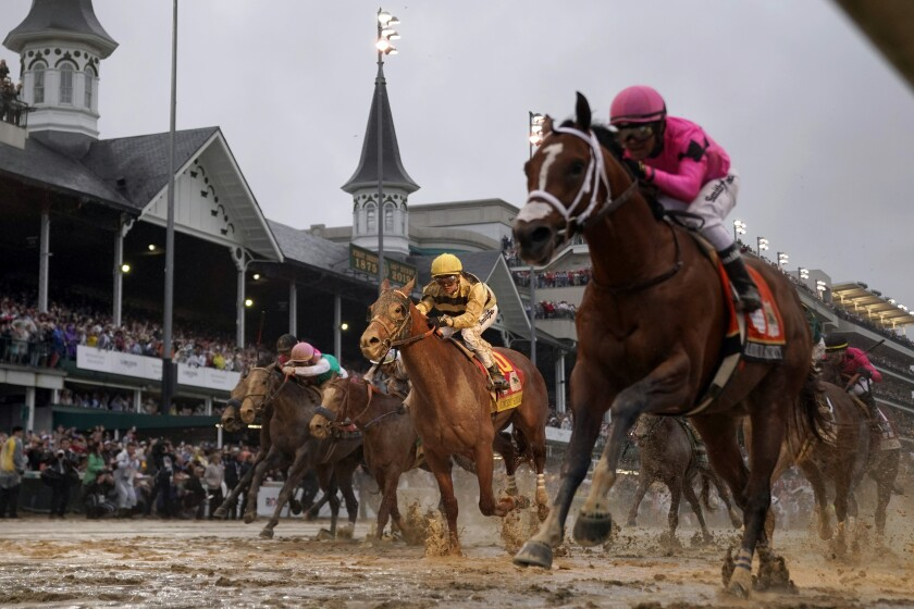 FILE - In this May 4, 2019, file photo, jockey Flavien Prat, aboard Country House, center, looks on as jockey Luis Saez, right, aboard Maximum Security, crosses the finish line during the 145th running of the Kentucky Derby horse race at Churchill Downs in Louisville, Ky. Maximum Security crossed the finish line first in the 2019 Kentucky Derby. What happened next set horse racing off on a year-long odyssey of chaos. From a historic DQ to doping, lawsuits to a global pandemic, and then a Triple Crown turned upside down. (AP Photo/Matt Slocum, File)
