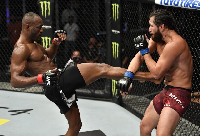 Kamaru Usman, left, kicks Jorge Masvidal during UFC 251 on Sunday on Yas Island, United Arab Emirates.