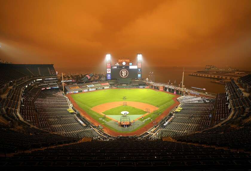 Smoke from California wildfires obscures the sky over Oracle Park as the Seattle Mariners take batting practice before their baseball game against the San Francisco Giants on Wednesday, Sept. 9, 2020, in San Francisco. People from San Francisco to Seattle woke Wednesday to hazy clouds of smoke lingering in the air, darkening the sky to an eerie orange glow that kept street lights illuminated into midday, all thanks to dozens of wildfires throughout the West. (AP Photo/Tony Avelar)