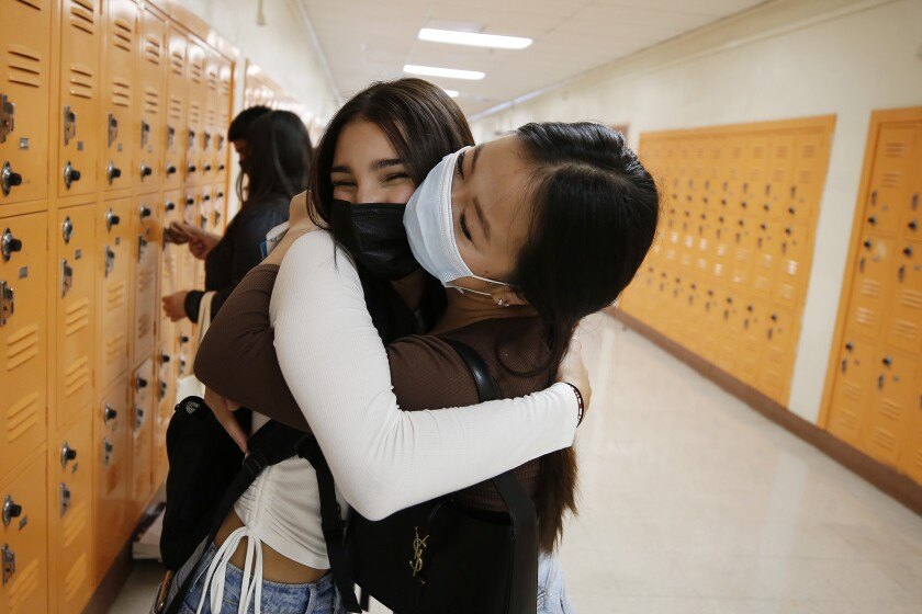 LOS ANGELES, CA - AUGUST 11: Abraham Lincoln High School Senior Tristan Gamboa, hugs friend Karen Gu as seniors are allowed to enter campus Wednesday morning to receive class selection, school ID, locker assignment and pick up books for classes. Tristan dreams of attending a Cal State University. She struggled to get good grades her freshman year, but was improving her sophomore year. When schools shut their doors in the spring that year, she stayed home as family and friends were sickened by COVID-19, finding it difficult to concentrate. LAUSD is planning to reopen in person instruction next Monday, August 16 with high safety standards and protocols at every campus for the 2021-22 school year. Abraham Lincoln High School on Wednesday, Aug. 11, 2021 in Los Angeles, CA. (Al Seib / Los Angeles Times).