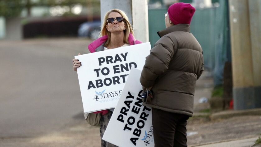 Kami Bullock, left, and Barbara Beavers, both antiabortion activists, hold signs outside the Jackson Women's Health Organization clinic in Jackson, Miss. on March 8.