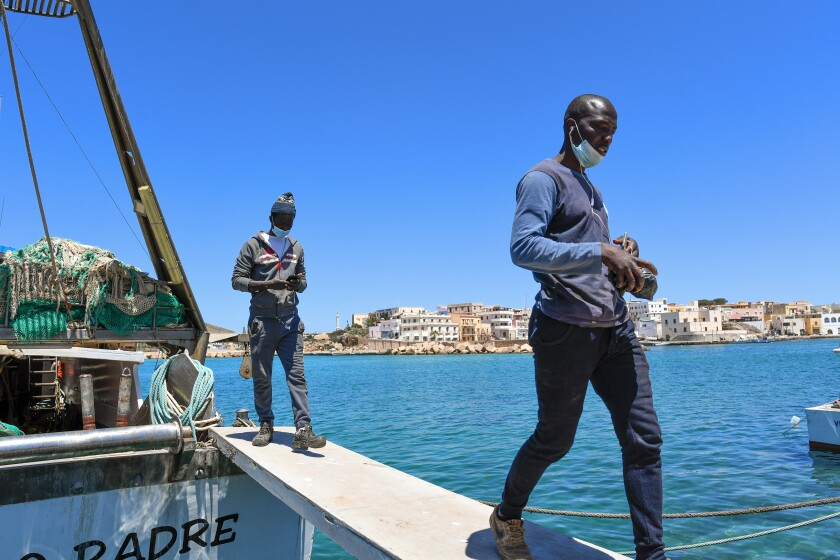 """Waly Sarr, 30, left, and Ibrahima Mbaye, 41, both from Senegal, walk off the """"Vincenzo Padre"""" fishing boat where they work as fishermen, in the Island of Lampedusa, southern Italy, Thursday, May 13, 2021. The tiny island of Lampedusa, which is closer to Africa than the Italian mainland, is in the throes of yet another season of migrant arrivals, and Mbaye and Sarr can only watch from shore as their fellow African countrymen risk their lives to get here via smugglers' boats. (AP Photo/Salvatore Cavalli)"""