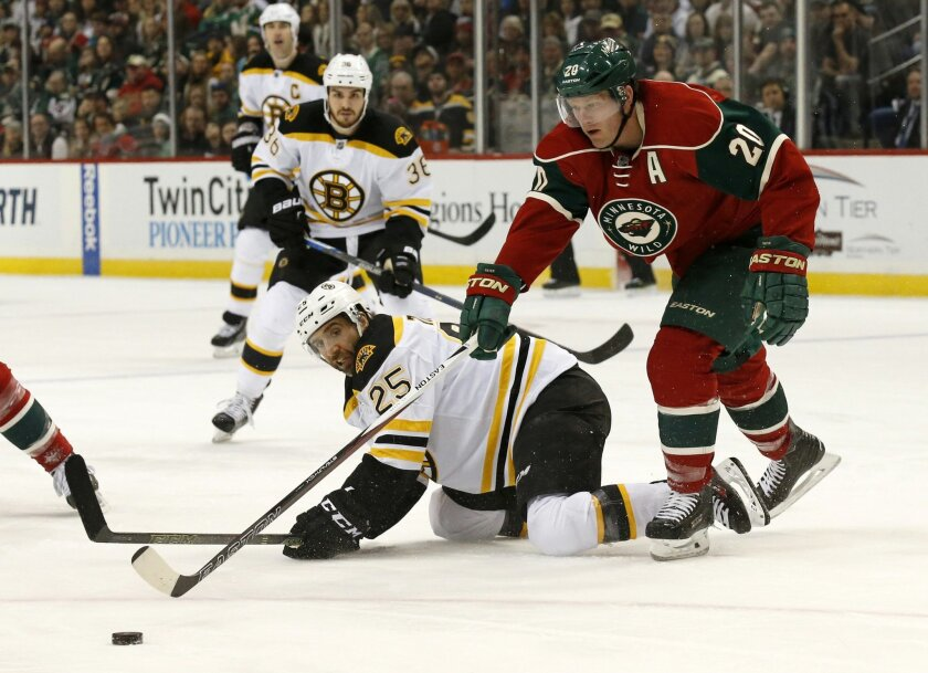 Minnesota Wild defenseman Ryan Suter (20) reaches for the puck in front of Boston Bruins center Max Talbot (25) during the second period of an NHL hockey game in St. Paul, Minn., Saturday, Feb. 13, 2016. (AP Photo/Ann Heisenfelt)