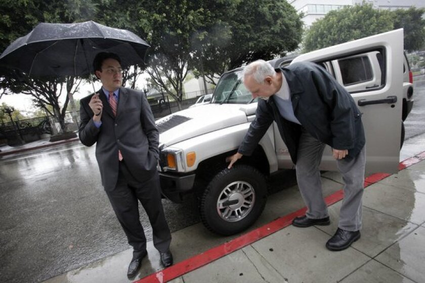 A 2010 photo shows Jaime de la Vega, left, then deputy mayor of Los Angeles, standing next to his Hummer SUV as Los Angeles Times columnist Steve Lopez examines the vehicle.