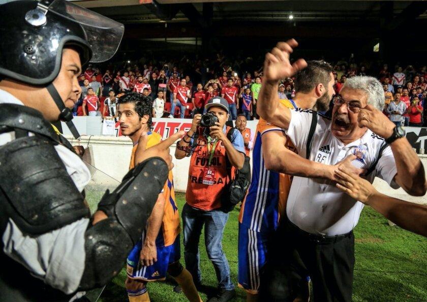 Tuca Ferretti se encara con un policía, a quien reclamó no dar seguridad a los fan de los Tigres.