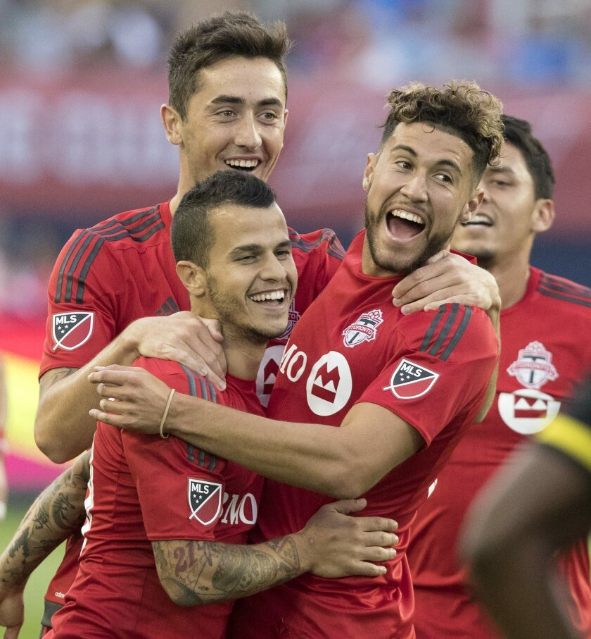 Teammates celebrate with Toronto FC's Sebastian Giovinco, lower left, after he scored the first of two goals against the Columbus Crew during the first half of an MLS soccer game Sunday, July 31, 2016, in Toronto. (Fred Thornhill/The Canadian Press via AP)