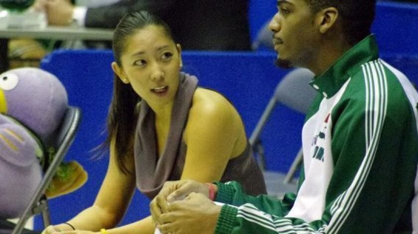 Natalie Nakase, left, coach of the Saitama Broncos, a mens basketball team in Japan, with player Joh