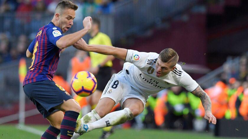 Barcelona midfielder Arthur, left, battles Real Madrid midfielder Toni Kroos for possession of the ball during a La Liga game on Oct. 28.