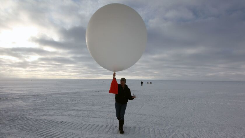 In this July 15, 2011 photo, atop roughly two miles of ice, technician Marie Mclane launches a data–