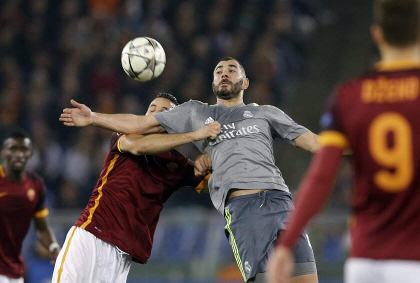 Real Madrid's Karim Benzema, right, jumps for the ball with Roma's Kostantinos Manolas   during a Champions League, round of 16, first-leg soccer match between Roma and Real Madrid, at the Rome Olympic stadium, Wednesday, Feb. 17, 2016. (AP Photo/Alessandra Tarantino)