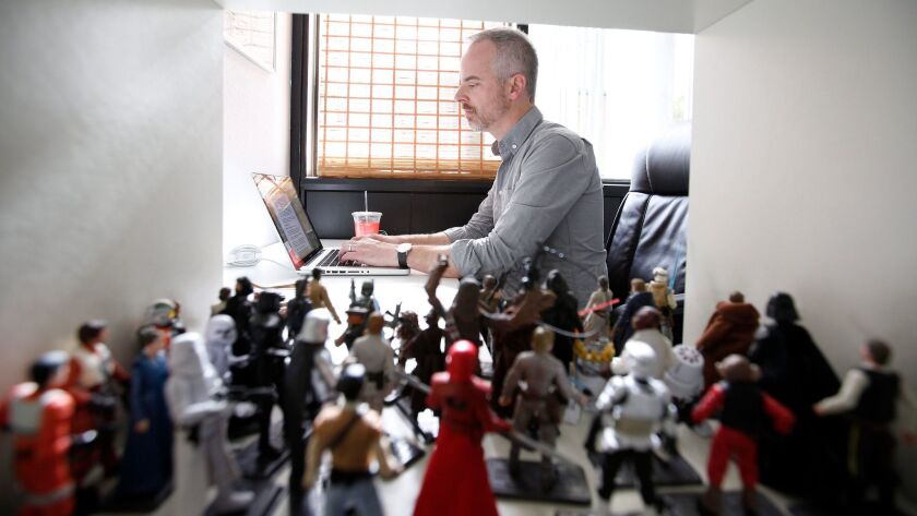 Writer John Gary works beside a collection of Star Wars figurines.