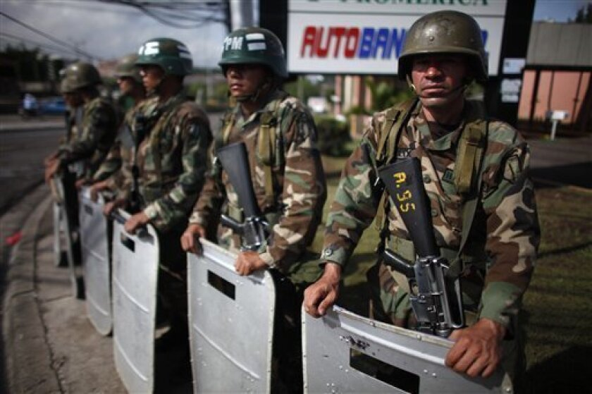 Soldiers stand guard on a corner near the presidential residence in Tegucigalpa, Wednesday, July 1, 2009. Honduras' interim leader, Roberto Micheletti, warned that the only way ousted President Manuel Zelaya will return to office is through a foreign invasion but a potential showdown was postponed when Zelaya delayed his plans to return to Honduras.(AP Photo/Dario Lopez-Mills)