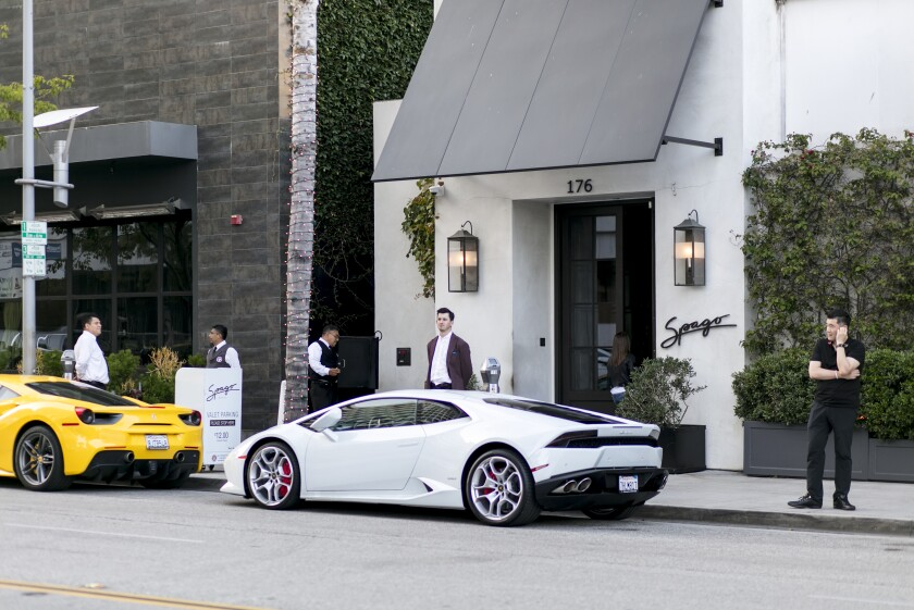 Spago's crisp exterior in Beverly Hills with luxury sports cars at the door.