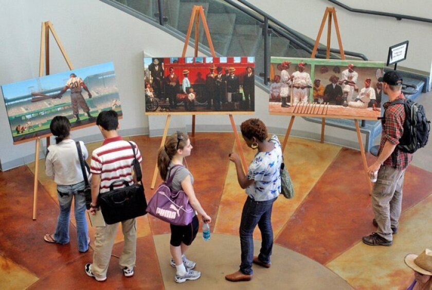 Visitors at Grossmont College view artwork by Kadir Nelson, who created two stamps for the U.S. Postal Service commemorating Negro Leagues baseball.