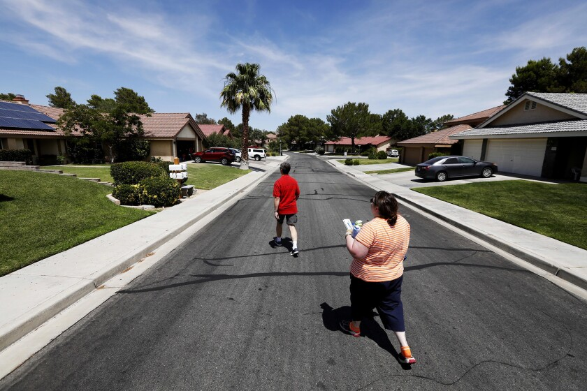 Kristina Stockmyer and her husband Mark walk back to their home in the Heritage Village community of Ridgecrest, Calif., where most of the structures stayed intact after a pair of earthquakes hit the area last week.