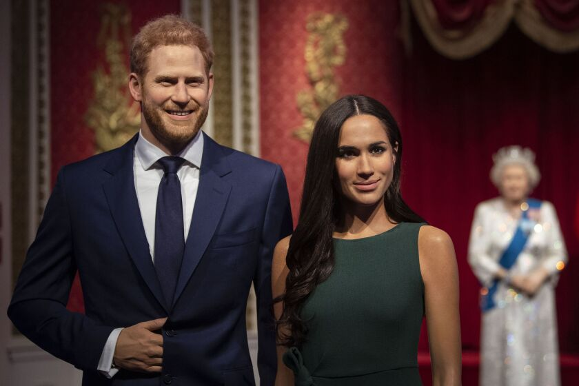 The figures of Britain's Prince Harry and Meghan, Duchess of Sussex, left, are moved from their original positions next to Queen Elizabeth II, Prince Philip and Prince William and Kate, Duchess of Cambridge, at Madame Tussauds in London, Thursday Jan. 9, 2020. Madame Tussauds moved its figures of Prince Harry and Meghan, Duchess of Sussex from its Royal Family set to elsewhere in the attraction. (Victoria Jones/PA via AP)