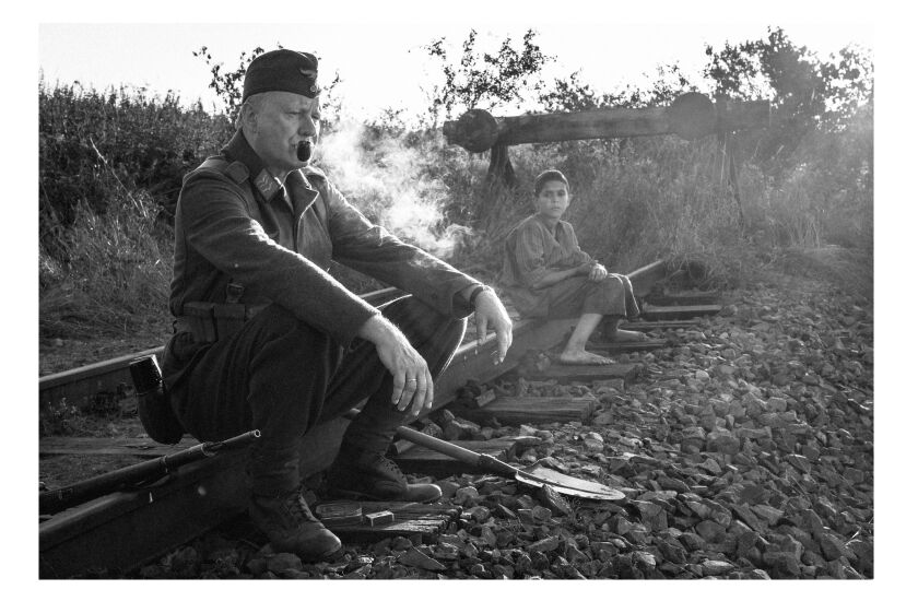 "Stellan Skarsgård and Petr Kotlár sit on the train tracks in ""The Painted Bird."""