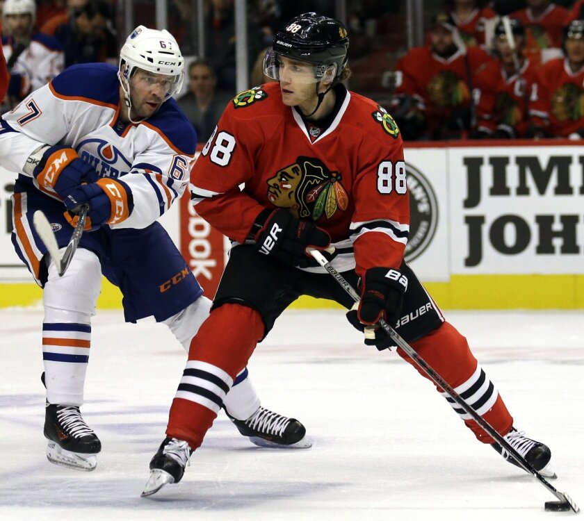 Chicago Blackhawks right wing Patrick Kane, right, looks to a pass against Edmonton Oilers left wing Benoit Pouliot during the first period of an NHL hockey game, Sunday, Nov. 8, 2015,  in Chicago. (AP Photo/Nam Y. Huh)