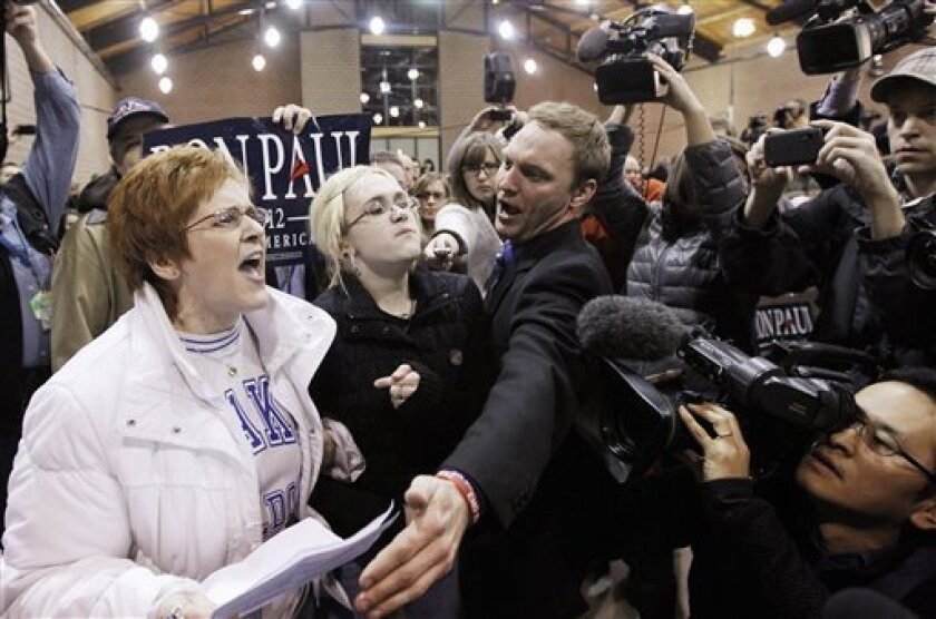 Occupy protesters, left, disrupt the speech of Republican presidential candidate, Rep. Ron Paul, R-Texas, as he campaigns during an event honoring veterans at the Iowa State Fair Grounds in Des Moines, Iowa, Wednesday, Dec. 28, 2011. (AP Photo/Charles Dharapak)