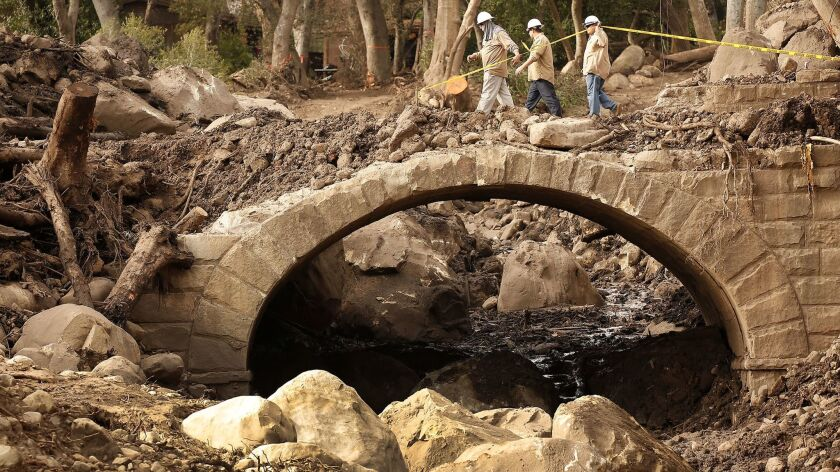 Workers carefully cross the Ashley Road Bridge over Montecito Creek as crews clear debris, attempt to restore power and reopen roadways.