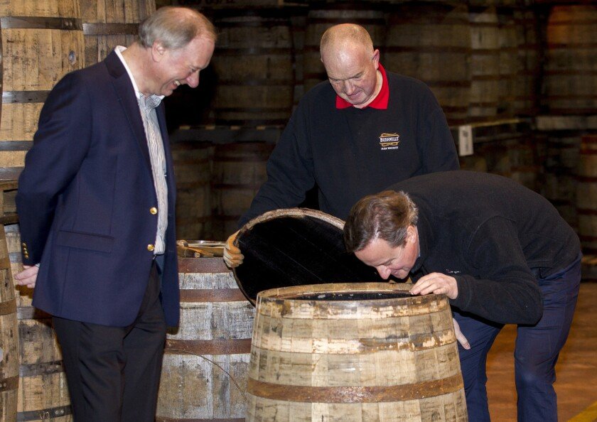 British Prime Minister David Cameron smells a whiskey barrel during a visit to the Bushmills distillery in Northern Ireland on Feb. 27.