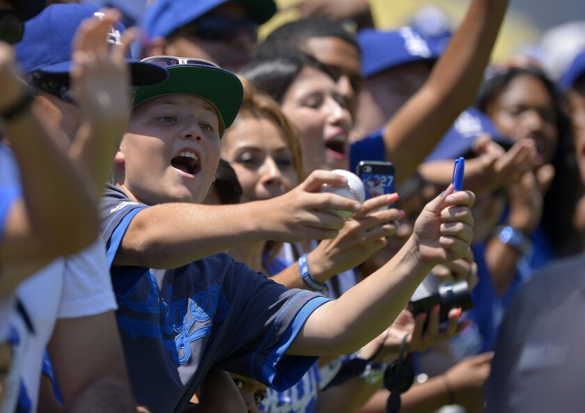 Dodgers fans try to get autographs from players before a game against the Colorado Rockies in July.
