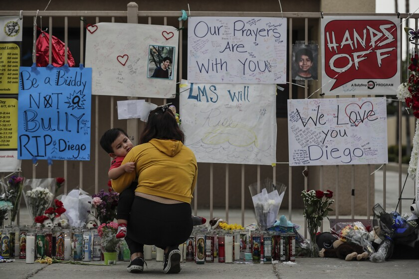 Vivian Ortiz and her son visit a memorial to a student at Landmark Middle School in Moreno Valley on Sept. 26, 2019.