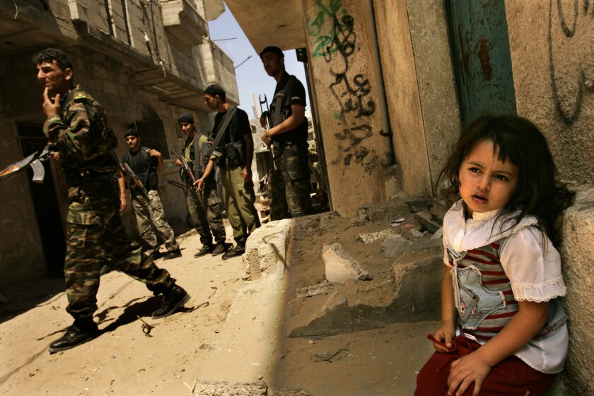SECURITY CHECK: Palestinian troops search for a live explosive device near the fringes of a Jewish settlement in the Gaza Strip. Lila , 4, a Palestinian girl who lives nearby, seems unfazed.