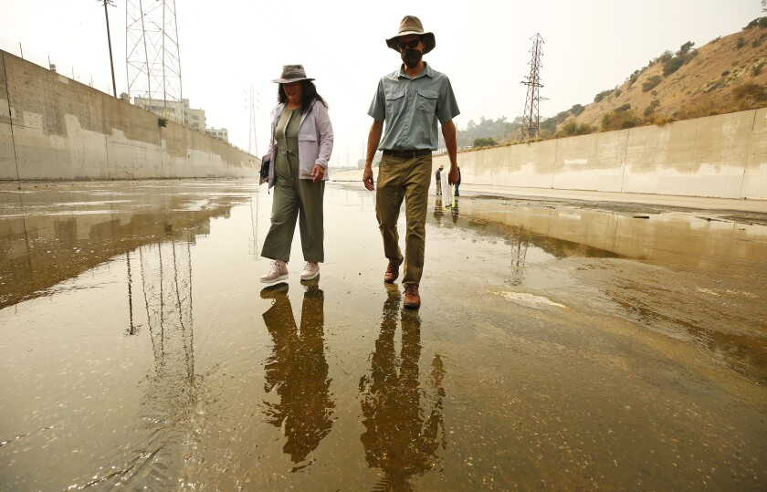 Wendy Katagi and Isaac Brown walk in the concrete-lined L.A. River channel.