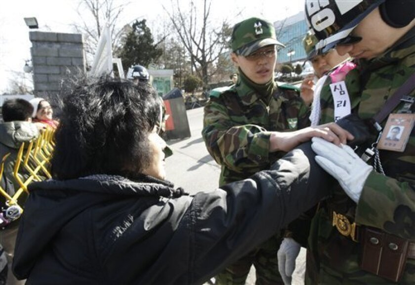 A South Korean anti-war protester gives a flower to an army soldier during a rally against South Korean activists who  launched propaganda leaflets toward North Korea, at a main gate of Defense Ministry in Seoul, South Korea, Wednesday, March 2, 2011. South Korean activists say they will continue l