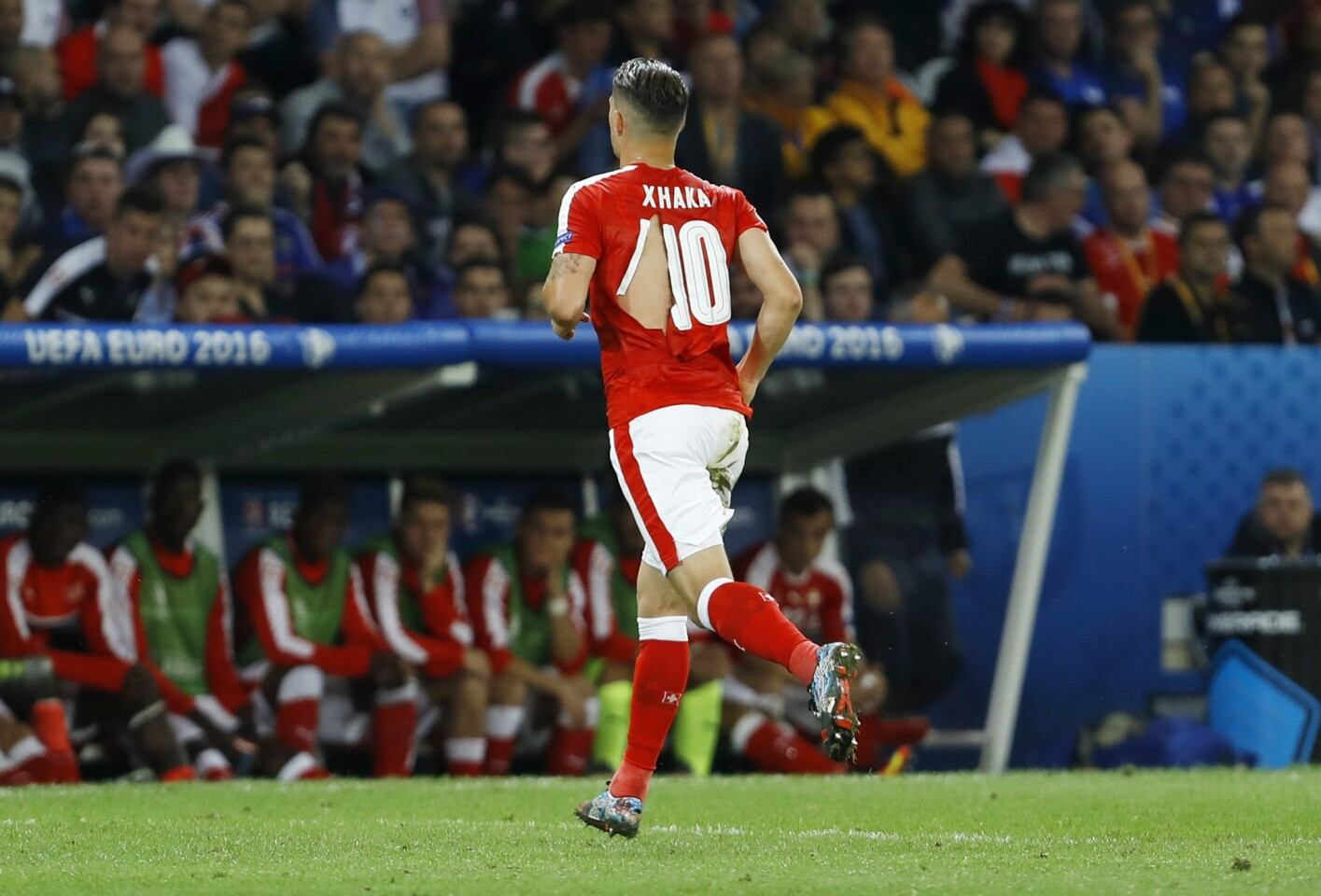 Switzerland's Granit Xhaka runs to the bench and change his ripped jersey during the Euro 2016 Group A soccer match between Switzerland and France at the Pierre Mauroy stadium in Villeneuve d'Ascq, near Lille, France, Sunday, June 19, 2016. (AP Photo/Darko Vojinovic)