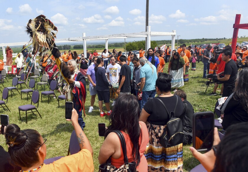 Tribal elder Duane Hollow Horn Bear leads a procession in honor of the nine Rosebud children whose remains are being transported home Friday, July 16, 2021 at the Fort Randall Casino on the Yankton Sioux Reservation in South Dakota. The disinterred remains of nine Native American children who died more than a century ago while attending a government-run school in Pennsylvania are headed home to Rosebud Sioux tribal lands in South Dakota. (Erin Bormett/The Argus Leader via AP)