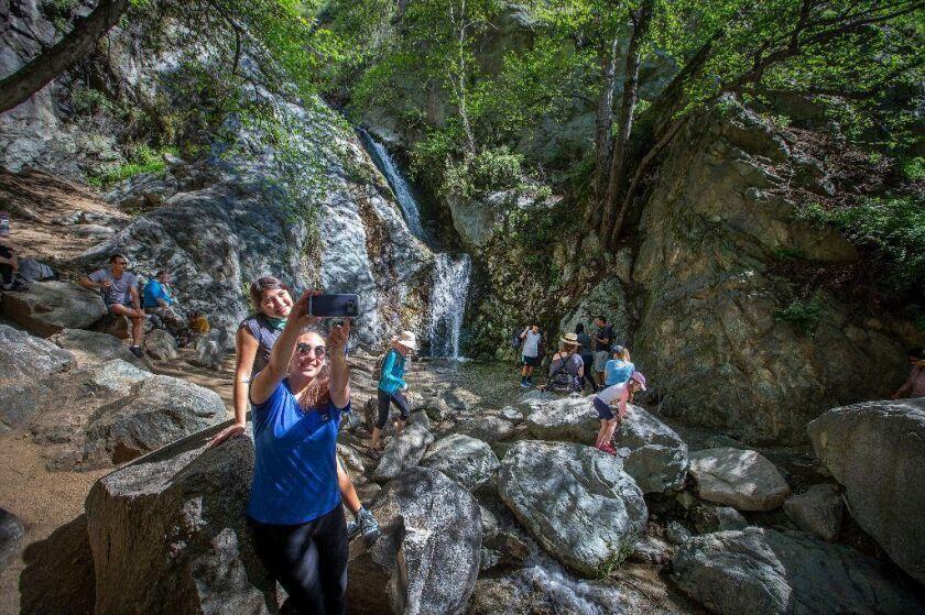 Hikers take photos and explore the Monrovia Canyon Falls in Monrovia, Calif.