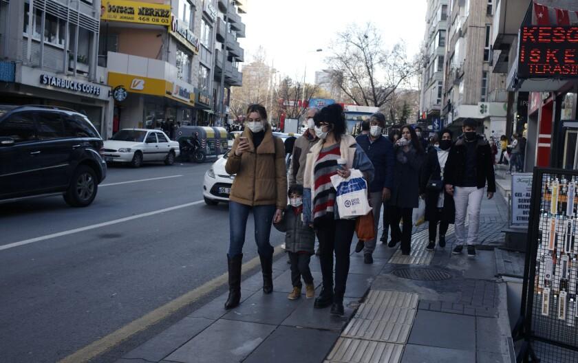 Unas personas con cubrebocas por el coronavirus caminan por una calle de comercios en Ankara, Turquía, el miércoles 30 de diciembre de 2020. (AP Foto/Burhan Ozbilici)