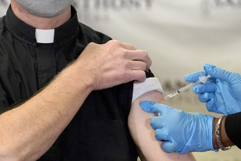 FILE - In this Wednesday, Dec. 23, 2020 file photo, a Catholic pastor receives the first of the two Pfizer-BioNTech COVID-19 vaccinations at a hospital in Chicago. In a growing consensus, religious leaders at the forefront of the anti-abortion movement in the United States are telling their followers that the leading vaccines available to combat COVID-19 are acceptable to take, given their remote and indirect connection to lines of cells derived from aborted fetuses. (AP Photo/Charles Rex Arbogast)