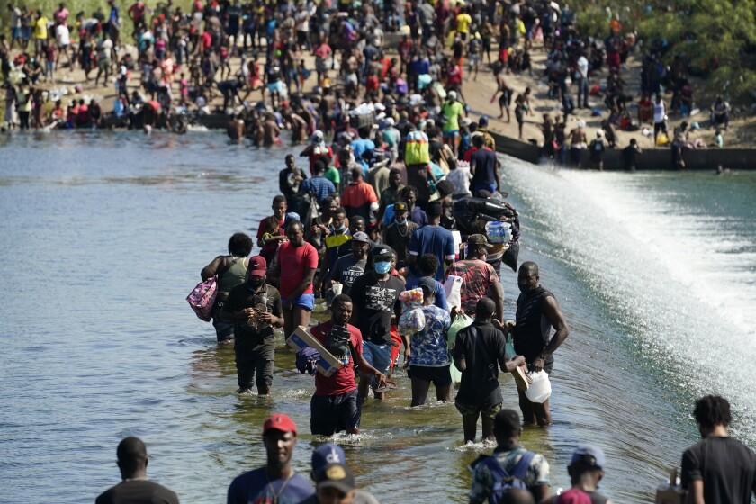 People wade through water.