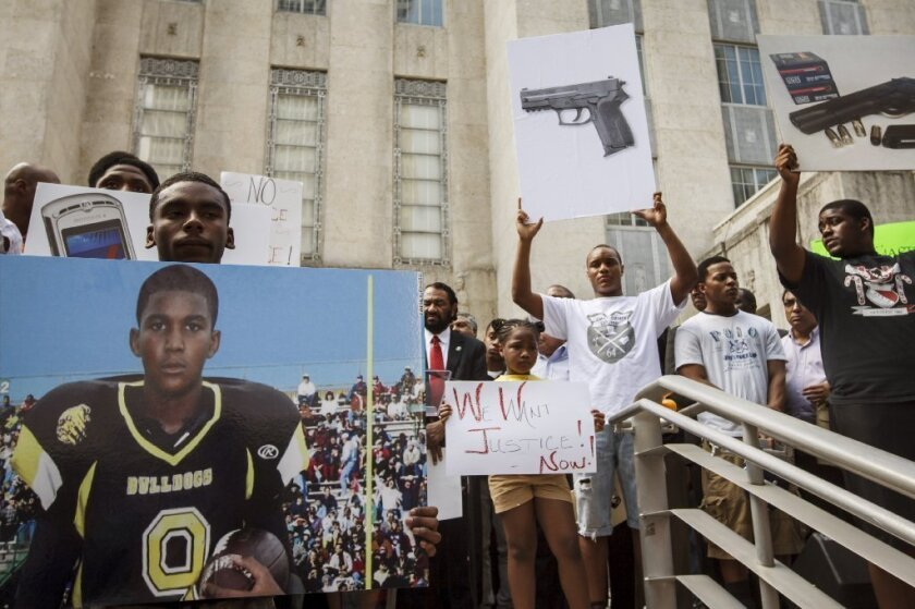 Demonstrators hold signs in support of Trayvon Martin during a March 2012 rally outside of City Hall in Houston.