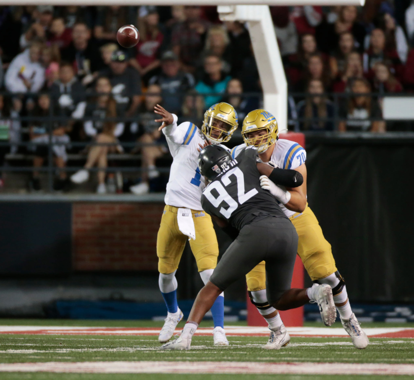 UCLA lineman Alec Anderson protects quarterback Dorian Thompson-Robinson from Washington State's Will Rodgers III in 2019.