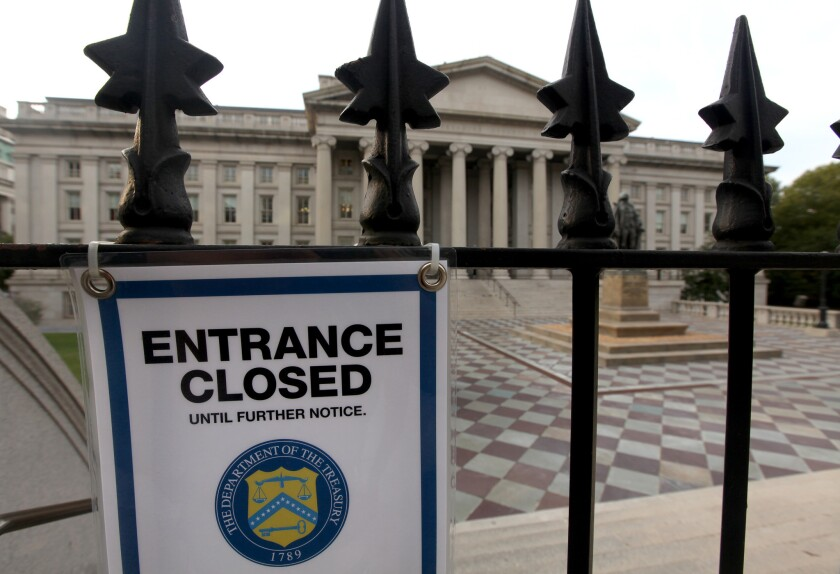"A ""closed"" sign hangs at the entrance to the U.S. Treasury building in Washington."
