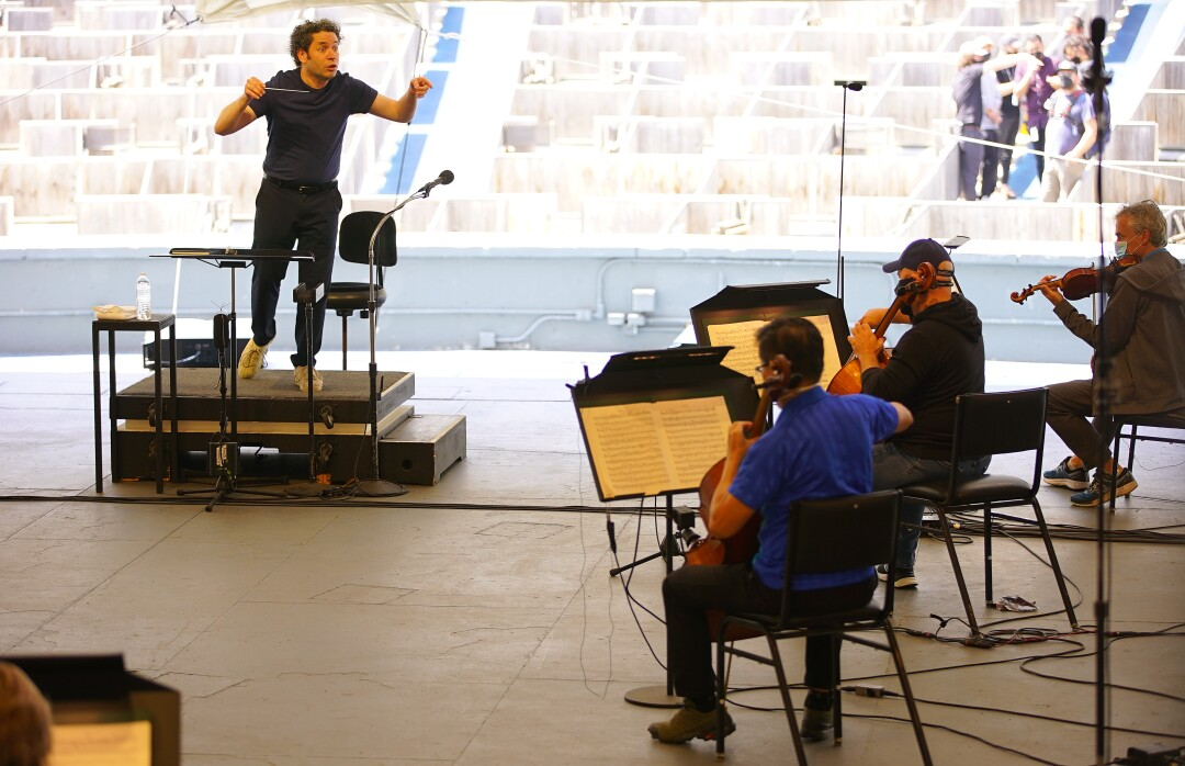 Dudamel holds up his hands as he conducts rehearsal