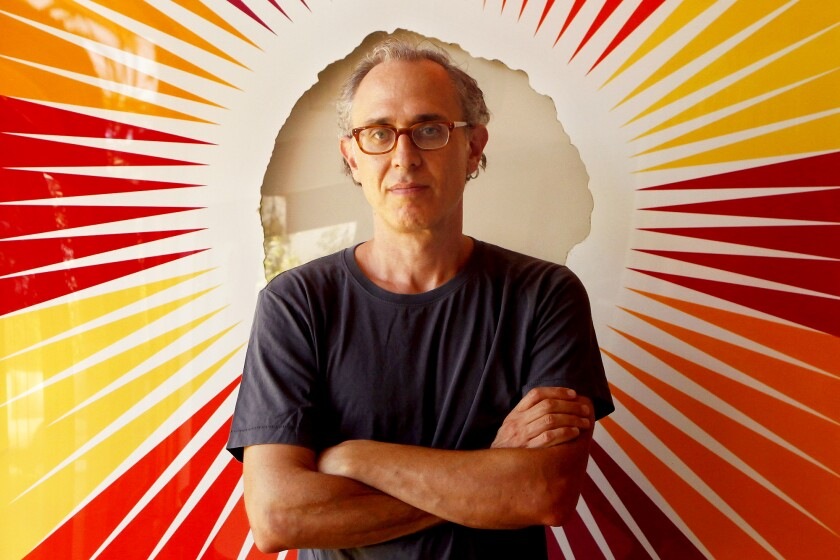 A portrait of Joshua Wolf Shenk, wearing glasses, a T-shirt and with his arms crossed