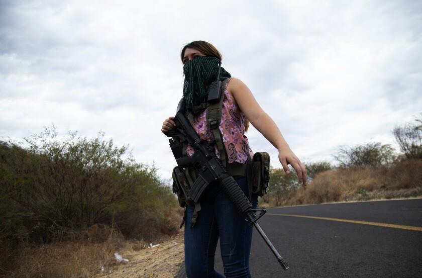 Una mujer armada vigila las afueras de El Terrero, en el estado de Michoacán, México