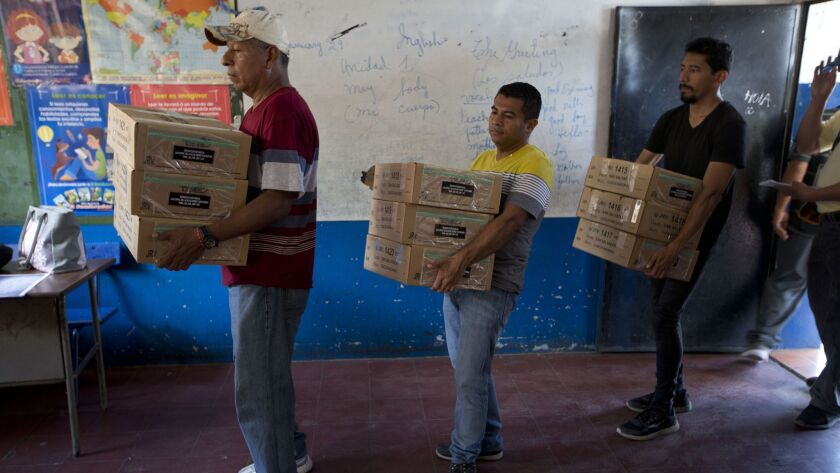 Electoral volunteers unload boxes filled with ballots at a polling station at a school on the outski