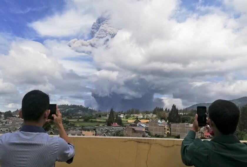 Dos personas toman fotos al volcán Sinabung mientras hace erupción en Karo, Indonesia
