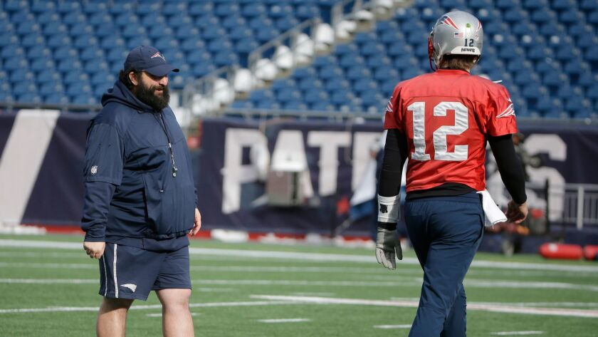 Patriots quarterback Tom Brady walks on the field during practice Tuesday in front of defensive coordinator Matt Patricia.
