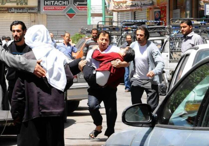 A man runs with one of the injured after an explosion in Damascus, the Syrian capital. The official Syrian news agency reported that at least 13 people were killed and more than 70 were injured.