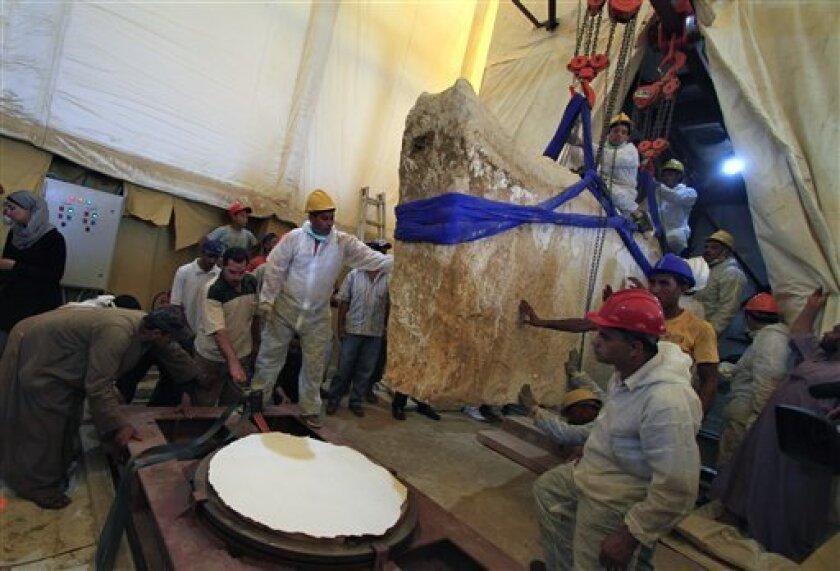 An Egyptian and Japanese team of scientists use a pulley system to lift the first of 41 16-ton limestone slabs to reveal fragments of the ancient ship of King Khufu next to the Great Pyramid of Giza, Egypt, Thursday, June 23, 2011. Archaeologists have begun the excavation process of a 4,500-year old wooden boat encased underground next to the Great Pyramid of Giza, Egyptologists announced Thursday.(AP Photo/Khalil Hamra)